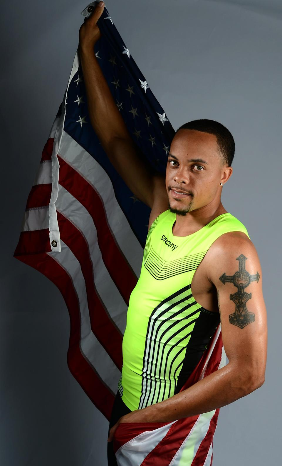 "Sprinter Wallace Spearmon of the US Track and Field Olympic team poses for pictures during the 2012 Team USA Media Summit on May 13, 2012 in Dallas,Texas. The detailed crucifix on his left bicep complements the ""Naturally gifted naturally"" tattoo on his right arm. JOE KLAMAR/AFP/GettyImages"