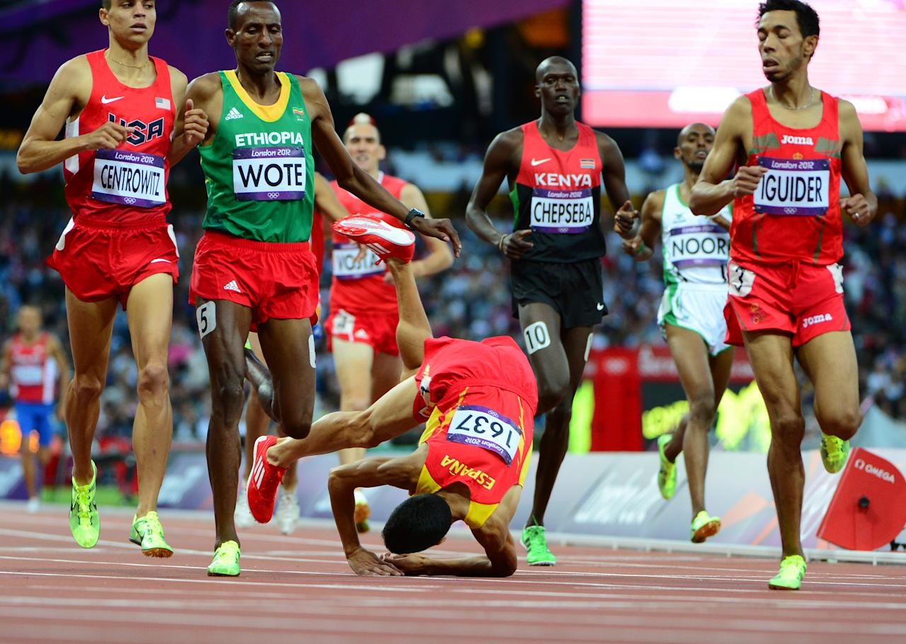 Spain's Diego Ruiz (C) falls during in the men's 1500m heats at the athletics event during the London 2012 Olympic Games on August 3, 2012 in London.  AFP PHOTO / OLIVIER MORIN