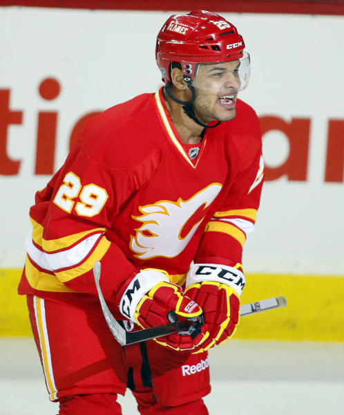 """FILE - In this April 7, 2012, file photo, Calgary Flames' Akim Aliu, a Nigerian-born Canadian, celebrates his goal during first period NHL hockey action against the Anaheim Ducks, in Calgary, Alberta. Calgary Flames general manager Brad Treliving said the team is looking into an accusation that head coach Bill Peters directed racial slurs toward a Nigerian-born hockey player a decade ago in the minor leagues, then arranged for the player's demotion when he complained. Akim Aliu tweeted Monday, Nov. 25, 2019, that Peters """"dropped the N bomb several times towards me in the dressing room in my rookie year because he didn't like my choice of music."""" (AP Photo/The Canadian Press, Jeff McIntosh, File)"""