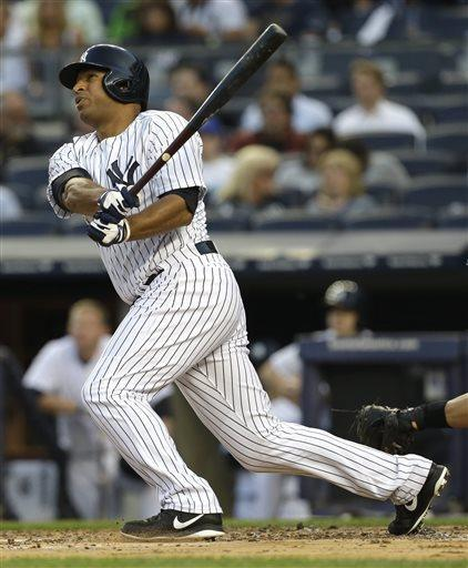 New York Yankees' Vernon Wells follows through on a home run off Seattle Mariners starting pitcher Hisashi Iwakuma during the first inning of a baseball game at Yankee Stadium in New York, Wednesday, May 15, 2013. (AP Photo/Julio Cortez)