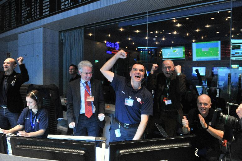FILE - In this photo provided by the European Space Agency, ESA, Monday Jan. 20, 2014 technicians celebrate after receiving the Rosetta wake up signal in the control room of ESA in Darmstadt, Germany. Waking up after almost three years of hibernation, a comet-chasing spacecraft sent its first signal back to Earth on Monday, prompting cheers from scientists who hope to use it to achieve the first landing on a comet.The European Space Agency received the all-clear message from its Rosetta spacecraft at 7:18 p.m. (1818 GMT; 1:18 p.m. EST) _ a message that had to travel some 800 million kilometers (500 million miles). (AP Photo/ESA, Juergen Mai, File)
