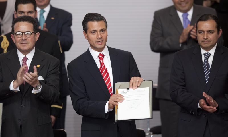 FILE - In this March 11, 2013 file photo, Mexico's President Enrique Pena Nieto, center, is flanked by Mexican Senate Deputy Chairman Francisco Arroyo Vieira, left, and Mexican Senate President Ernesto Cordero as he shows an agreement signed by him and the three major political parties that would create two new national television stations and form a powerful independent regulatory commission, along the lines of the U.S. Federal Communications Commission, in Mexico City. Pena Nieto has been fast out of the blocks in attacking some of Mexico's toughest issues in a country often stymied by monopolies and corruption. He says his plan will make the country more democratic and competitive in the world economy, and his drive for reform is fueling international confidence about Mexico. (AP Photo/Alexandre Meneghini, file)