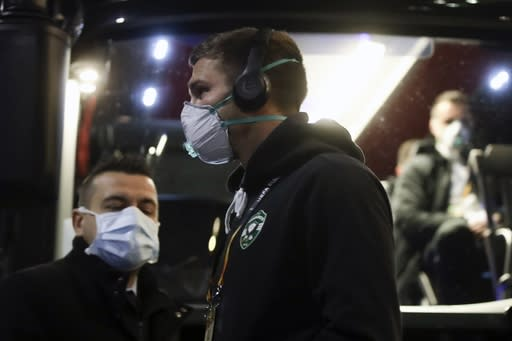 Bulgarian soccer team Ludogorets, wearing protective face masks get on a coach bus heading to the San Siro stadium in Milan, Italy, Thursday, Feb. 27, 2020. Ludogorets is playing Italian club Inter Milan in a Europa League soccer match on Thursday that is scheduled to go ahead in an empty stadium due to the coronavirus outbreak. (AP Photo/Luca Bruno)