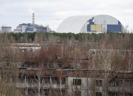 A containment shelter for the damaged fourth reactor (L) and the New Safe Confinement (NSC) structure (R) at the Chernobyl Nuclear Power Plant are seen from Ukraine's abandoned town of Pripyat, Ukraine, March 23, 2016. REUTERS/Gleb Garanich