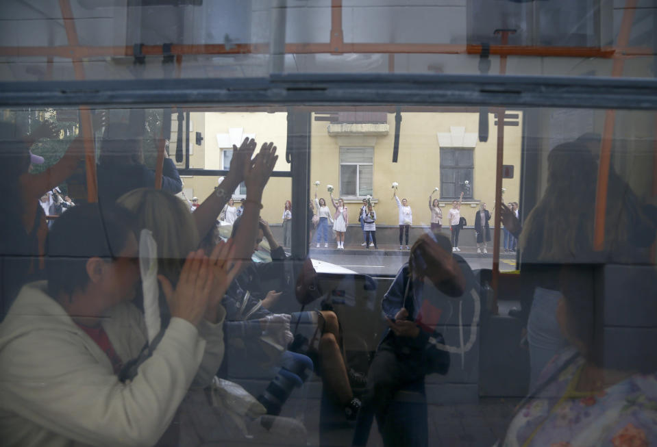 "Belarusian passengers applaud through a bus window to women who taking part in a rally in solidarity with protesters injured in the latest rallies against the results of the country's presidential election while two men on a balcony greet them in Minsk, Belarus, Thursday, Aug. 13, 2020. Hundreds of people were back on the streets of Belarus' capital on Thursday morning, forming long ""lines of solidarity"" in protest against an election they say was rigged to extend the rule of the country's authoritarian leader and against a crackdown on rallies that followed the vote. (AP Photo/Sergei Grits)"