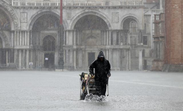 A greengrocer carries his cart as the water begins to flood St. Mark's Square on the occasion of a high tide, in Venice, Italy, Tuesday, Nov. 12, 2019. (Photo: Luca Bruno/AP)