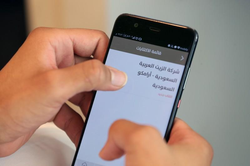 A Saudi man checks his mobile phone following the start of Aramco IPO, in Riyadh