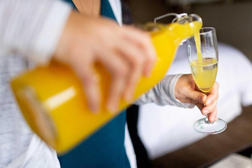 Woman pouring orange juice into champagne in glass to make mimosa