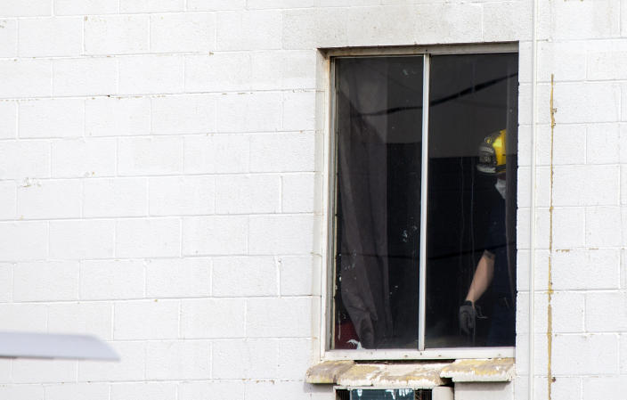 Las Vegas firefighter stands by a window after a fatal fire at a three-story apartment complex early Saturday, Dec. 21, 2019 in Las Vegas. The fire was in first-floor unit of the Alpine Motel Apartments and its cause was under investigation, the department said. Authorities say multiple fatalities were reported and several were injured. (Steve Marcus/Las Vegas Sun via AP)