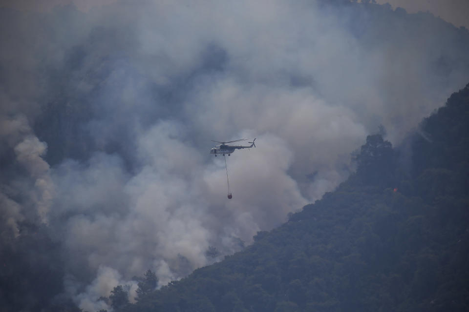 A firefighting helicopter flies over a wildfire that burns the forest in Turgut village, near tourist resort of Marmaris, Mugla, Turkey, Wednesday, Aug. 4, 2021. As Turkish fire crews pressed ahead Tuesday with their weeklong battle against blazes tearing through forests and villages on the country's southern coast, President Recep Tayyip Erdogan's government faced increased criticism over its apparent poor response and inadequate preparedness for large-scale wildfires.(AP Photo/Emre Tazegul)