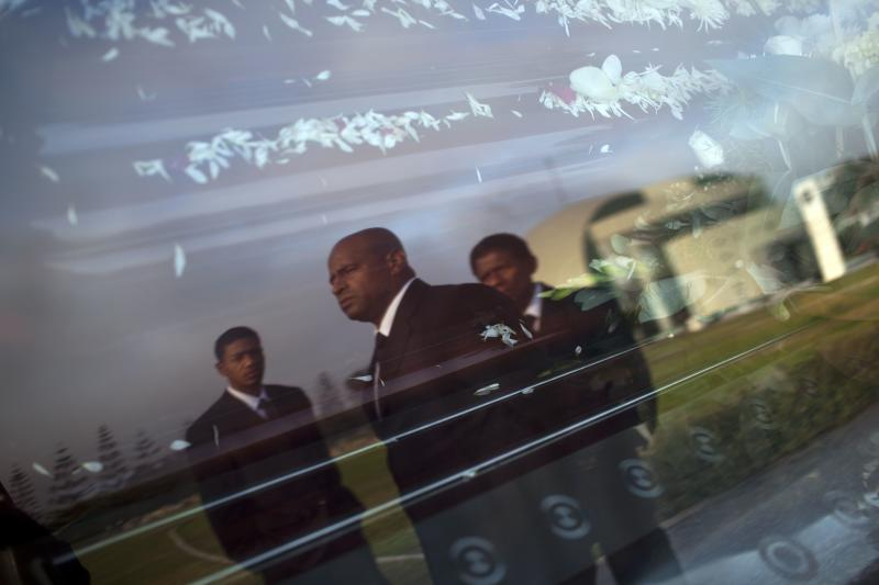 In this May 11, 2013 photo, the reflection of black pallbearers Hertor Fano, center, Victor Rivas, right, and Victor's nephew Alex Rivas, cover the window of a hearse as they work at a funeral in Lima, Peru. Blacks routinely bear the caskets of ex-presidents, mining magnates and bankers to their tombs in Lima. The peculiar tradition exists neither in provicinal Peruvian cities nor in other Latin American countries with significant black populations such as Brazil, Panama and Colombia. (AP Photo/Rodrigo Abd)