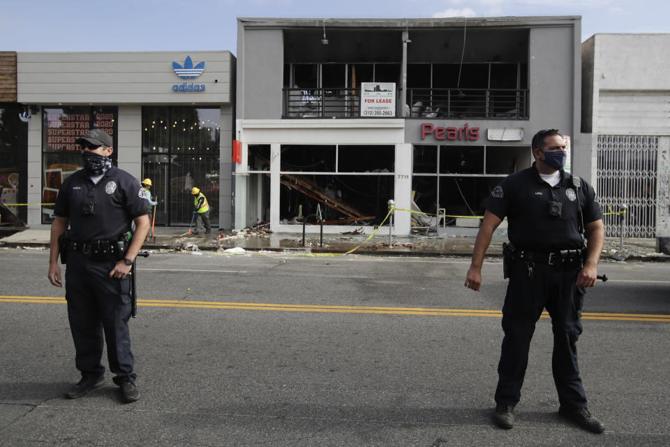 Police officers stand in front of a fire-damaged building, Sunday, May 31, 2020, in Los Angeles, following a night of unrest and protests over the death of George Floyd, a black man who was in police custody in Minneapolis. Floyd died after being restrained by Minneapolis police officers on May 25. (AP Photo/Marcio Jose Sanchez)
