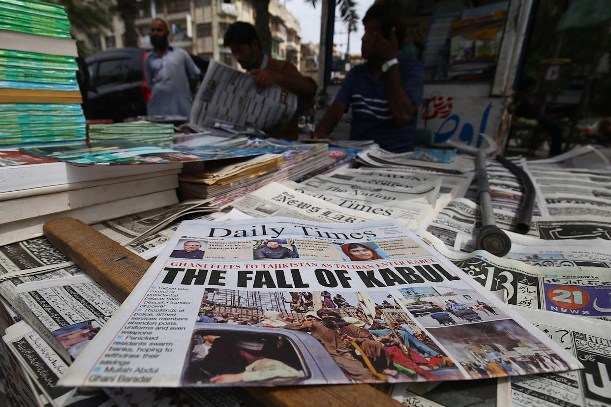 At a newspaper stall in Karachi, Pakistan, on Aug. 16, people read front-page news of the Taliban's takeover of Kabul.