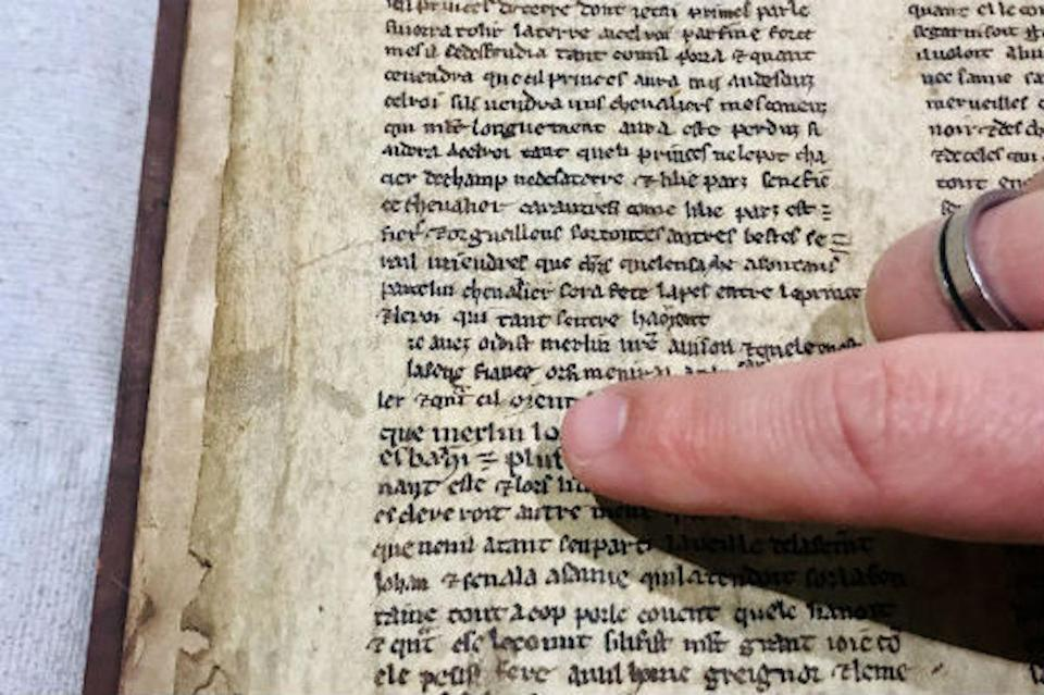 """A finger points to the name """"Merlin"""" on a page with text in a very old book"""