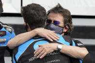 Team owner Wayne Taylor, right, hugs his son Ricky after winning the Rolex 24 hour auto race at Daytona International Speedway, Sunday, Jan. 31, 2021, in Daytona Beach, Fla. (AP Photo/John Raoux)