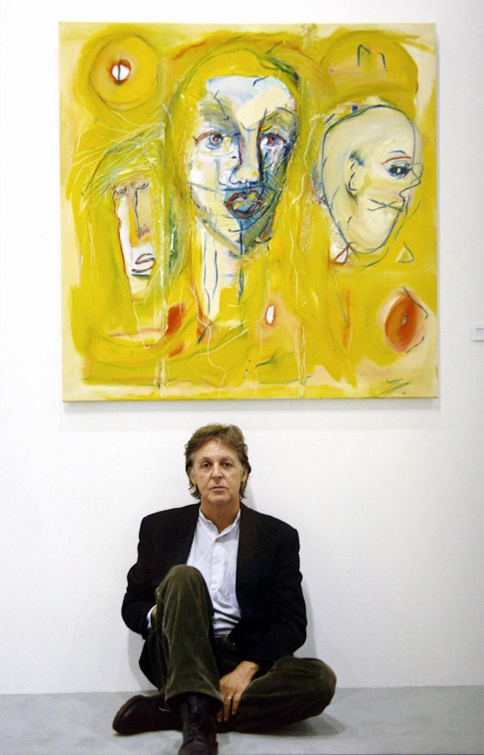 "Sir Paul McCartney sits in front of his oil painting ""Unspoken Words."""
