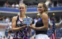 Elise Mertens, of Belgium, left, poses for photos with the trophy with doubles partner Arena Sabalenka, of Belarus, after winning the women's doubles final against Victoria Azarenka, of Belarus, and Ashleigh Barty, of Australia, at the U.S. Open tennis championships Sunday, Sept. 8, 2019, in New York. (AP Photo/Sarah Stier)