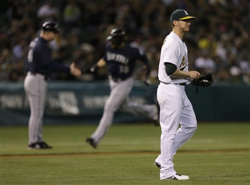 Oakland Athletics' Jarrod Parker, right, turns his back after giving up a three-run home run to Seattle Mariners' Michael Morse, center, in the third inning of a baseball game Tuesday, April 2, 2013, in Oakland, Calif. (AP Photo/Ben Margot)