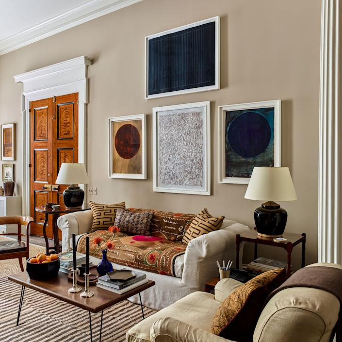 """<div class=""""caption""""> Architect Gil Schafer worked with his firm's interior design team to gently reimagine his Greenwich Village pied-à-terre with an eye to modernity. In the living room, a suzani sourced on a trip to Morocco enlivens the neutral-hued sofa, which is slipcovered in linen from <a href=""""https://arabelfabrics.com/"""" rel=""""nofollow noopener"""" target=""""_blank"""" data-ylk=""""slk:Arabel Fabrics"""" class=""""link rapid-noclick-resp"""">Arabel Fabrics</a> and flanked by a pair of lamps from <a href=""""https://sutterantiques.com/"""" rel=""""nofollow noopener"""" target=""""_blank"""" data-ylk=""""slk:Sutter Antiques"""" class=""""link rapid-noclick-resp"""">Sutter Antiques</a>. Artwork by Harrison Walker and Corey Daniels line the walls, and the custom cocktail table was fabricated by <a href=""""https://baba.com/"""" rel=""""nofollow noopener"""" target=""""_blank"""" data-ylk=""""slk:Baba Wood"""" class=""""link rapid-noclick-resp"""">Baba Wood</a>. </div>"""