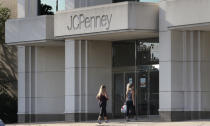 In this Wednesday, Aug. 14, 2019, photo two women walk into the JCPenney store in Peabody, Mass. J.C. Penney Co. on Thursday, Aug. 15, reported a loss of $48 million in its fiscal second quarter. (AP Photo/Charles Krupa)