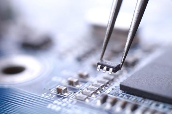 A technician installs a microchip on a circuit board with the help of tweezers.