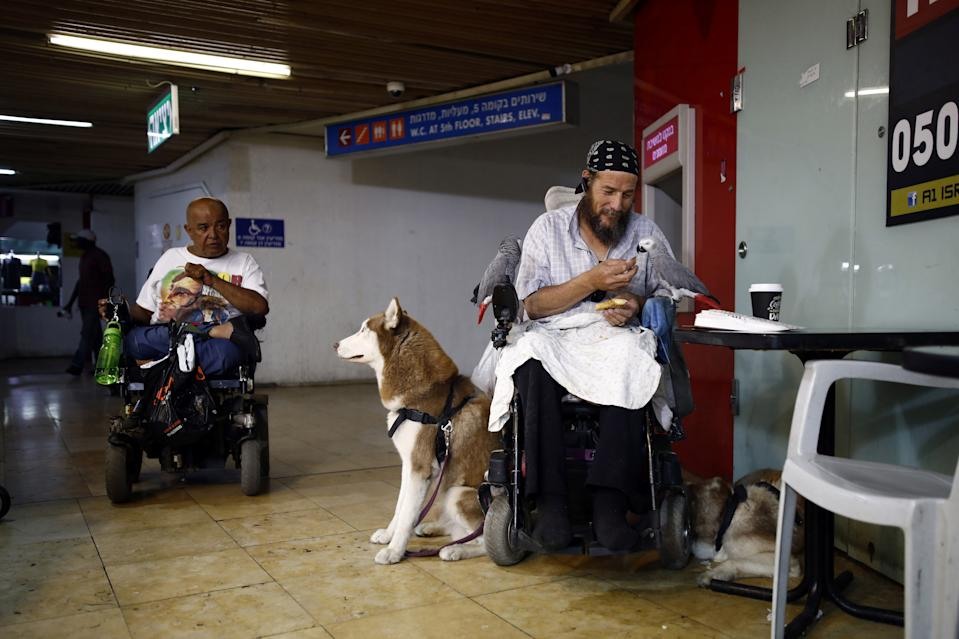 A man feeds his pet parrots at the Central Bus Station on May 29. (Photo: Corinna Kern/Reuters)
