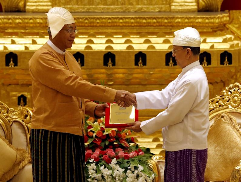 Myanmar's outgoing president Thein Sein (R) hands over the presidential seal to the country's new President Htin Kyaw (L) during the handover ceremony in Naypyidaw on March 30, 2016 (AFP Photo/Nyein Chan Naing/Pool)