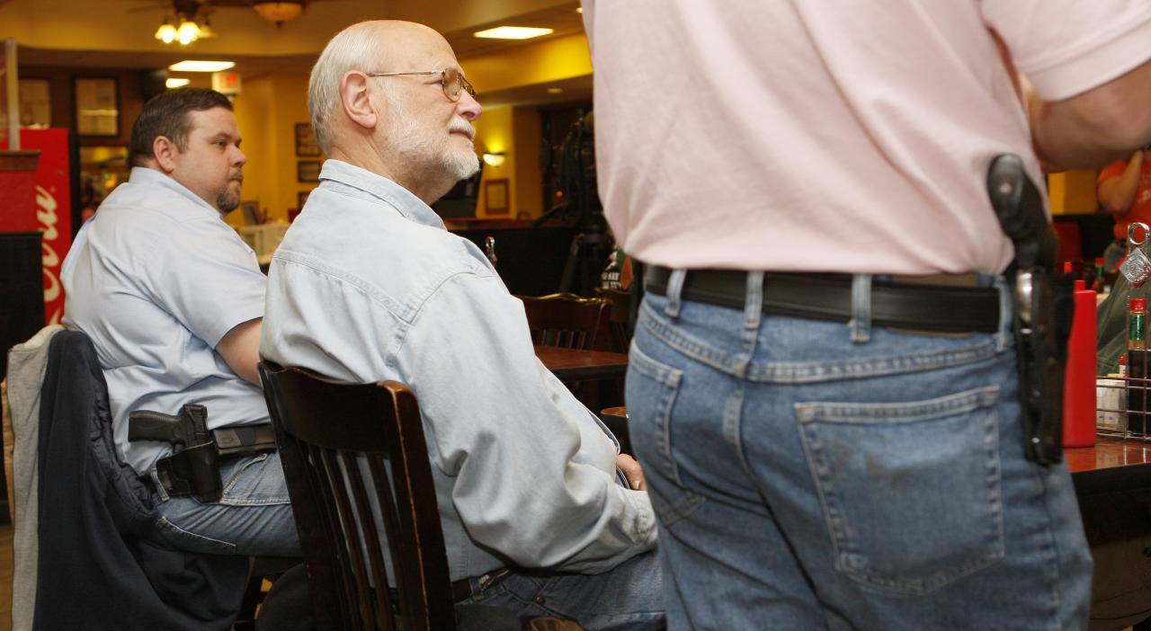 Bryan Hull (R), founding director of the Oklahoma Open Carry Association (OKOCA), and Tim Gillespie, director of Oklahoma Second Amendment Association, wear unconcealed side arms as Richard Prawdzienski (C) listens to Hull addressing OKOCA members gathered at Beverly's Pancake House in Oklahoma City November 1, 2012. A new Oklahoma law took effect November 1 allowing anyone with a concealed weapon license to carry their firearms openly in a holster or belt.   REUTERS/Bill Waugh   (UNITED STATES - Tags: SOCIETY POLITICS CRIME LAW)