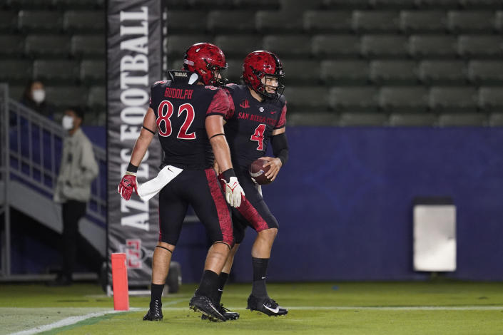San Diego State quarterback Jordon Brookshire (4) celebrates a touchdown with tight end Jay Rudolph (82) during the second half of an NCAA college football game against New Mexico Saturday, Oct. 9, 2021, in Carson, Calif. (AP Photo/Ashley Landis)