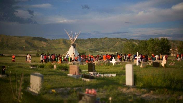 Hundreds of people gather for a vigil in a field where human remains were discovered in unmarked graves at the site of the former Marieval Indian Residential School on the Cowessess First Nation in Saskatchewan on June 26, 2021