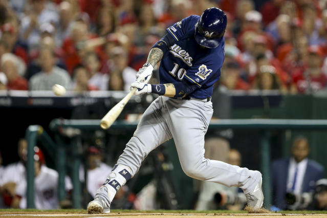 FILE - In this Oct. 1, 2019, file photo, Milwaukee Brewers Yasmani Grandal (10) hits a two-run home run during the first inning of a National League wild card baseball game against the Washington Nationals, at Nationals Park in Washington. All-Star catcher Yasmani Grandal agreed to a $73 million, four-year contract with the Chicago White Sox, finding a more lucrative free-agent market now that he no longer is burdened by draft-pick compensation. Grandal will earn $18.25 million annually as part of the deal announced Thursday, Nov. 21, 2019. (AP Photo/Andrew Harnik, File)