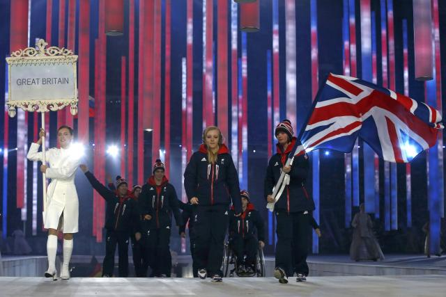 Britain's flag-bearer Millie Knight (R), leads his country's contingent during the opening ceremony of the 2014 Paralympic Winter Games in Sochi, March 7, 2014. REUTERS/Alexander Demianchuk (RUSSIA - Tags: OLYMPICS SPORT)