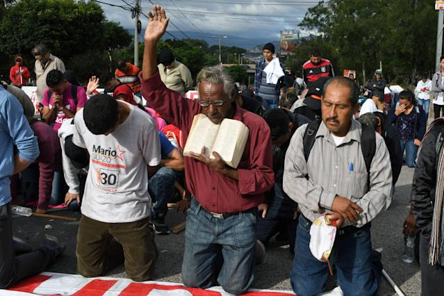 <p>Supporters of Honduran presidential candidate for the Opposition Alliance against the Dictatorship party Salvador Nasralla, kneel to pray during a protest near the Electoral Supreme Court (TSE), to demand the announcement of the election final results in Tegucigalpa, on Nov. 30, 2017. (Photo: Orlando Sierra/AFP/Getty Images) </p>