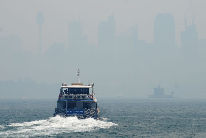 A ferry makes its way from Taronga Zoo to Circular Quay, with the CBD skyline barely visible in the background through smoke haze from bushfires, in Sydney Harbour