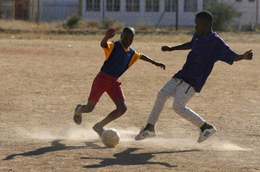 Young footballers play a friendly soccer match during practice in Winterveldt, South Africa, Sunday, June 17, 2018. Tebogo Mofokeng's legs were amputated when he was a toddler in South Africa, but that didn't stop him from fulfilling his dream of coaching young football players. Mofokeng, 18, is following the World Cup closely, but on Sunday morning he was on a dusty field in Winderveldt, a poor area northwest of the capital, Pretoria. (AP Photo/Denis Farrell)