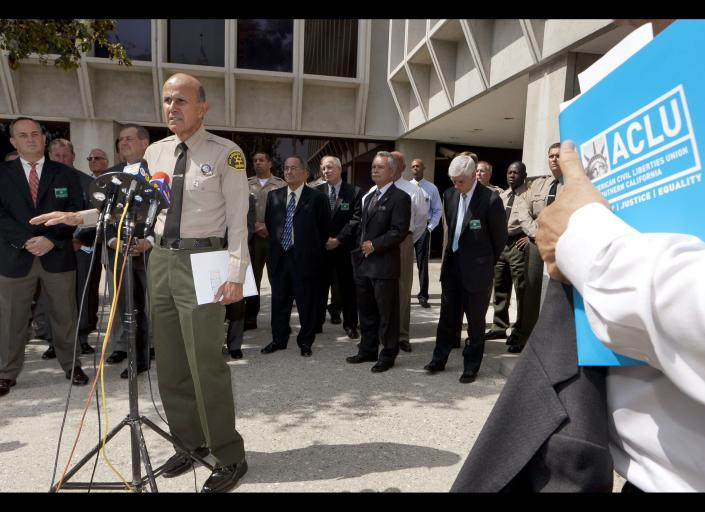 Los Angeles County Sheriff Lee Baca,at podium, takes questions about a report released by the American Civil Liberties Union, ACLU, outside Sheriff's headquarters Wednesday, Sept. 28, 2011, in Los Angeles. The ACLU demanded earlier Wednesday that federal authorities investigate allegations of brutality by deputies at Los Angeles County jails. (AP Photo/Damian Dovarganes)