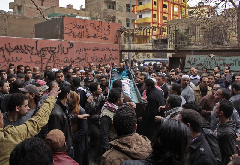 Egyptian relatives gather around the coffin of a man killed during Saturday's clashes between protesters and security forces at the Zeinhom morgue in Cairo, Egypt, Sunday, Jan. 26, 2014. Egyptian officials said Sunday that the death toll from clashes between security forces and protesters on the third anniversary of the country's 2011 uprising has risen to at least 49. (AP Photo/Aly Hazzaa, El Shorouk) EGYPT OUT
