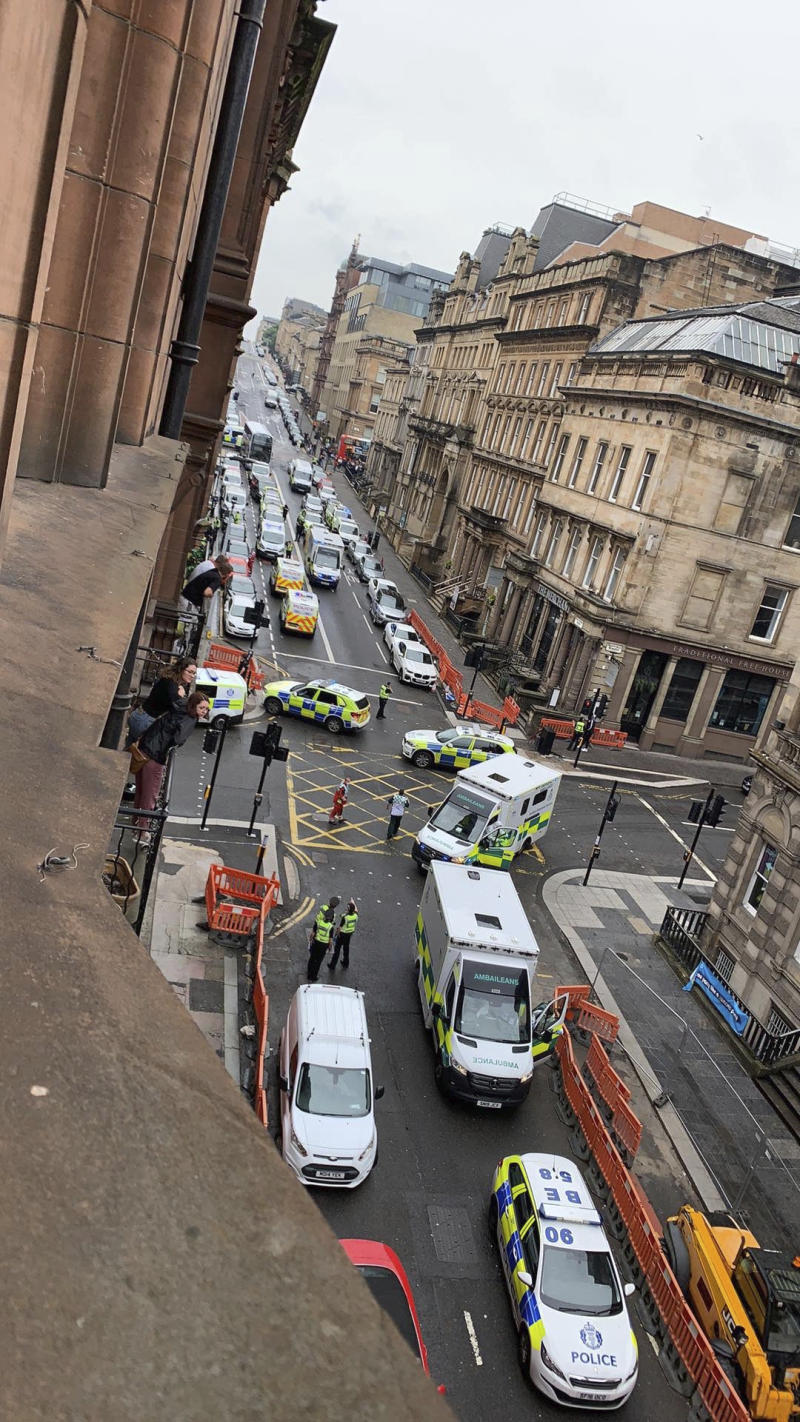 In this photo provided by the Twitter feed of @Milroy1717, emergency services attend the scene of incident in Glasgow, Scotland, Friday June 26, 2020. Police in Glasgow say emergency services are currently dealing with an incident in the center of Scotland's largest city and are urging people to avoid the area. (@Milroy1717 via AP)