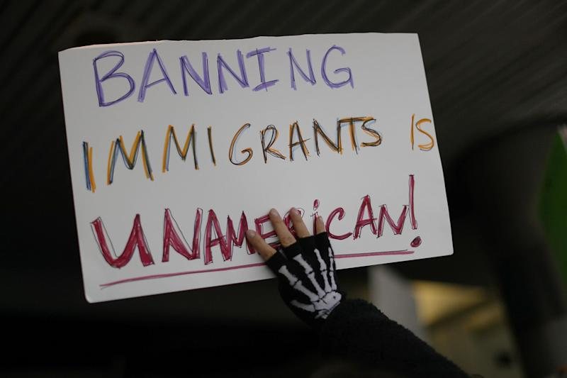 A protester holds up a sign that reads, 'Banning Immigrants is UnAmerican!,' as she stands with others at the Miami International Airport: Getty