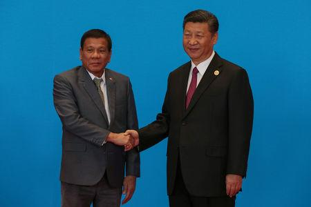 FILE PHOTO: Chinese President Xi Jinping shakes hands with Philippine President Rodrigo Duterte as they attend the welcome ceremony at Yanqi Lake during the Belt and Road Forum, in Beijing, China, May 15, 2017. REUTERS/Roman Pilipey/Pool