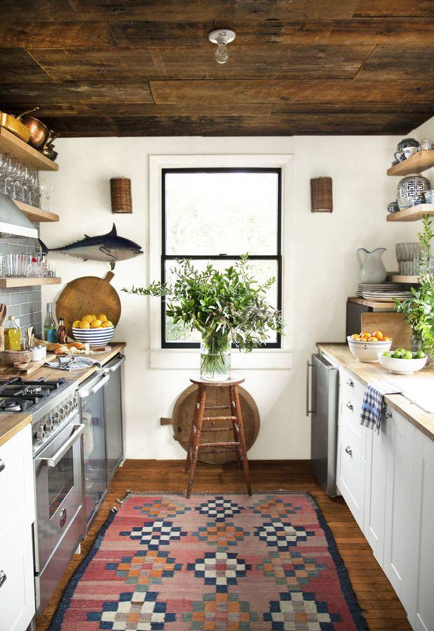 <p>Thanks to vintage finds and collected-over-time accessories, this charming coastal cottage kitchen is full of character. The black window trim and Aztec-inspired rug both bring a graphic touch to the otherwise rustic space. A pair of wicker sconces, bread boards, raw wood shelving, reclaimed wood-clad ceilings, and butcher block countertops add warmth to this cozy galley.</p>