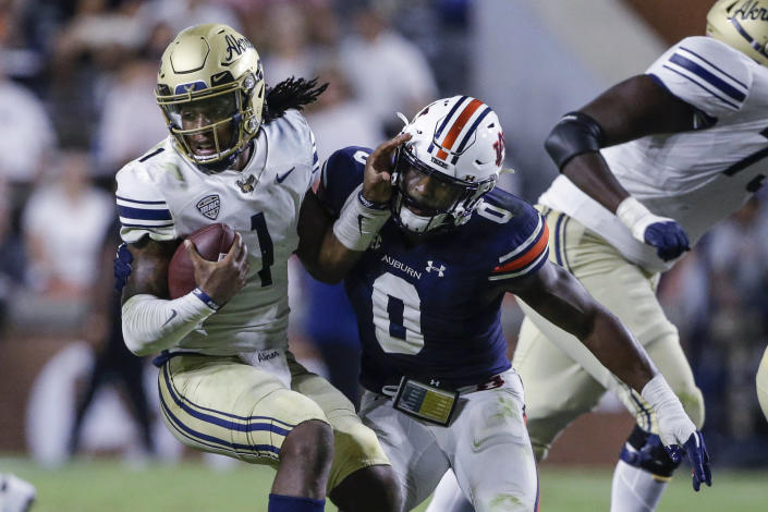 Akron quarterback Kato Nelson (1) escapes the pressure from Auburn linebacker Owen Pappoe (0) during the first half of an NCAA college football game Saturday, Sept. 4, 2021, in Auburn, Ala. (AP Photo/Butch Dill)