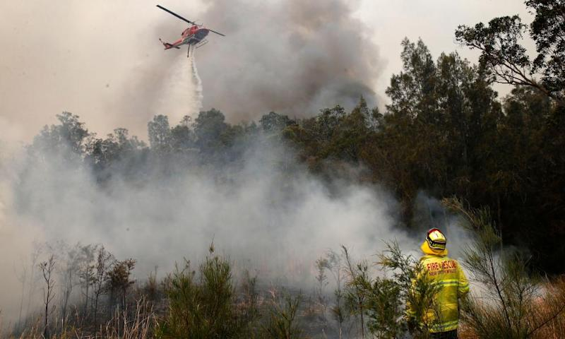 Firefighters work to contain a bushfire along Old Bar road in Old Bar, NSW.
