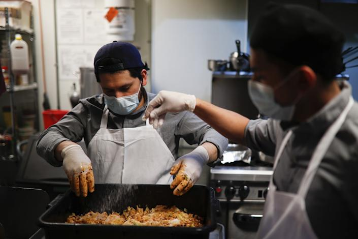 Kitchen worker Misael Cruz, 38, left, and Adam Rosas, 28, right, wear surgical masks and gloves as they prepare food
