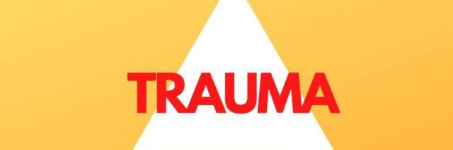 Photo of a white triangle on a yellow background with the words Trauma over it in red.