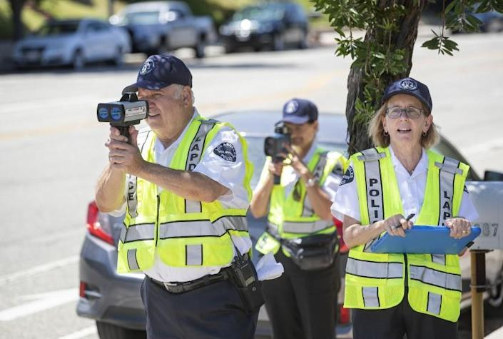 NORTHRIDGE, CA-JULY 24, 2019: left to right-Nishan Darakdjian, 73, and Karla Hanley, 68, use speed guns to catch motorists driving past the speed limit on Reseda Blvd. in Northridge as Amy Schneider, 63, writes down the speed they were going on July 25, 2019. They are volunteers with the Devonshire Community Police Station in Northridge. (Mel Melcon/Los Angeles Times)