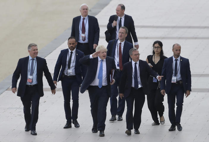 FILE - In this Monday, Aug. 26, 2019 file photo Britain's Prime Minister Boris Johnson, center, salutes people as he walks along the seafront in Biarritz, France ahead of the third and final day of the G-7 summit, . (AP Photo/Markus Schreiber)
