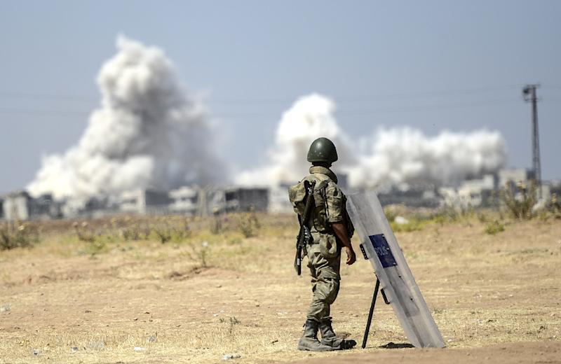 A Turkish solider watches as smoke rises from the Syrian border town of Kobane, on June 27, 2015