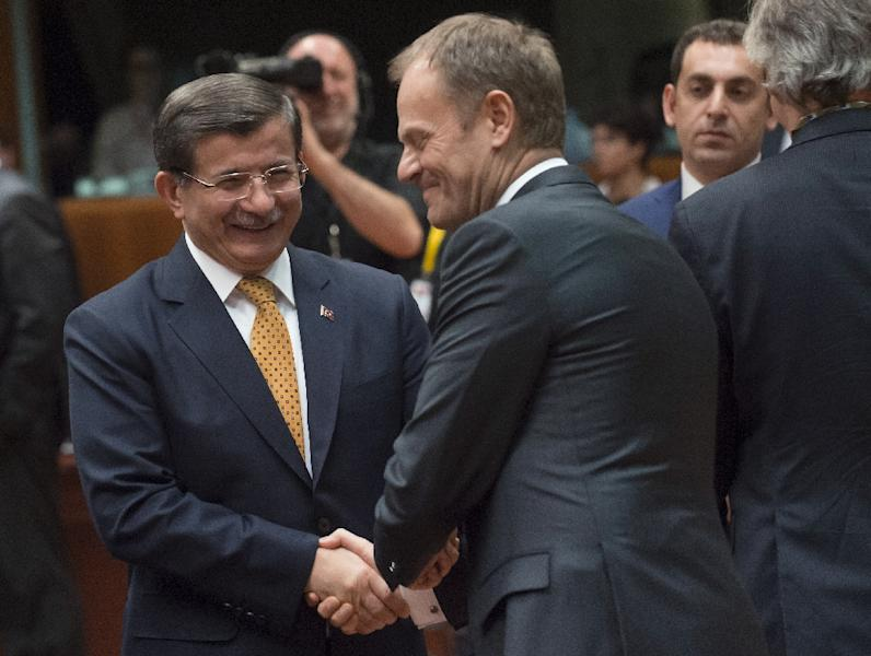 Turkey's Prime Minister Ahmet Davutoglu (L) talks with EU Council President Donald Tusk during the EU summit at headquarters in Brussels on March 18, 2016 (AFP Photo/John Thys)