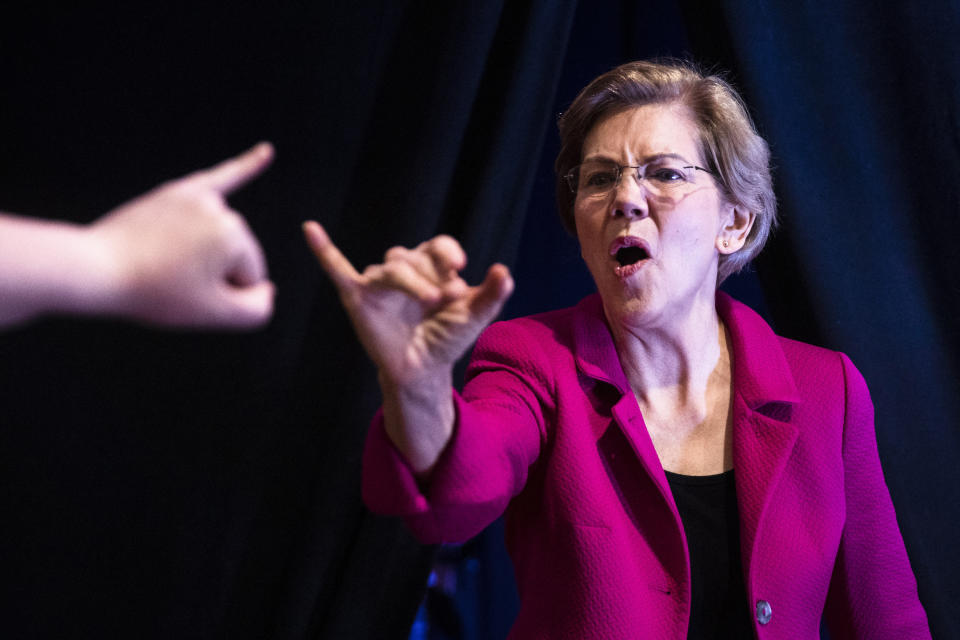 """Democratic presidential candidate Sen. Elizabeth Warren, D-Mass., locks pinky fingers with an attendee as she arrives to speak at """"Our Rights, Our Courts"""" forum New Hampshire Technical Institute's Concord Community College, Saturday, Feb. 8, 2020, in Concord, N.H. (AP Photo/Matt Rourke)"""